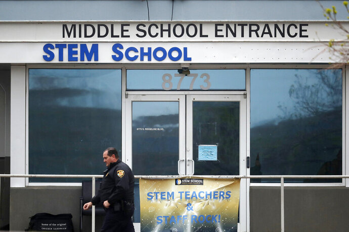 FILE - In this May 8, 2019, file photo, a Douglas County, Colo., Sheriff's deputy walks past the doors of the STEM Highlands Ranch school in Highlands Ranch, Colo. The younger of two students charged in the shooting at the suburban Denver school in the spring of 2019 is scheduled to be sentenced Friday, July 24, 2020. The decision will come after a hearing in which those impacted by the shooting, including the parents of a student who died trying to stop the attack at STEM School Highlands Ranch, will speak. (AP Photo/David Zalubowski, File)