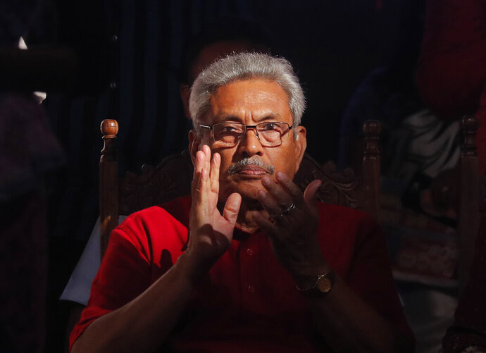 FILE- In this Nov. 13, 2019, file photo, Sri Lanka's former defense secretary and presidential candidate Gotabaya Rajapaksa attends a rally in Homagama, on the outskirts of Colombo, Sri Lanka. Rajapaksa is credited with helping end the country's long civil war and is revered as a hero by the Sinhalese Buddhist majority. He comfortably won Saturday's presidential election with about 52% of the ballots. But minorities largely voted for his opponent, fearing Rajapaksa because of allegations of wartime human rights violations against him. (AP Photo/Eranga Jayawardena, File)