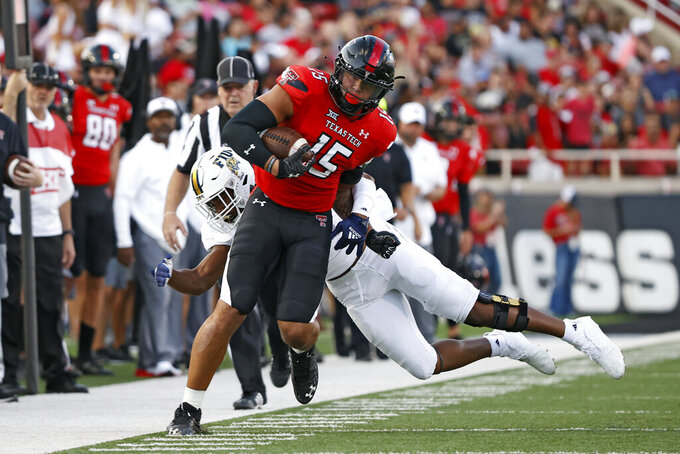 Florida International's Jamal Gates (9) tackles Texas Tech's Travis Koontz (15) during the first half of an NCAA college football game on Saturday, Sept. 18, 2021, in Lubbock, Texas. (AP Photo/Brad Tollefson)