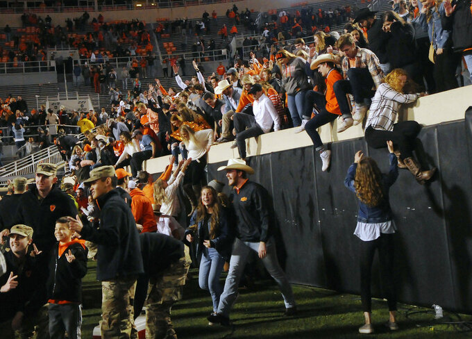 Oklahoma State fans stream over the barrier wall and onto the field following an NCAA college football game in Stillwater, Okla., Saturday, Nov. 17, 2018. Oklahoma State upset West Virginia 45-41.(AP Photo/Brody Schmidt)