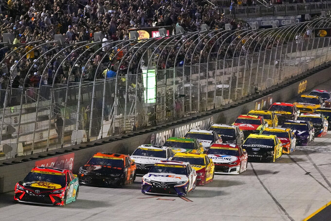 Martin Truex Jr. (19) leads the pack as they take the green flag to start a NASCAR Cup Series auto race at Bristol Motor Speedway Saturday, Sept. 18, 2021, in Bristol, Tenn. (AP Photo/Mark Humphrey)