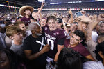 Texas A&M quarterback Zach Calzada (10) is surrounded by fans after the team's win over Alabama in an NCAA college football game Saturday, Oct. 9, 2021, in College Station, Texas. (AP Photo/Sam Craft)