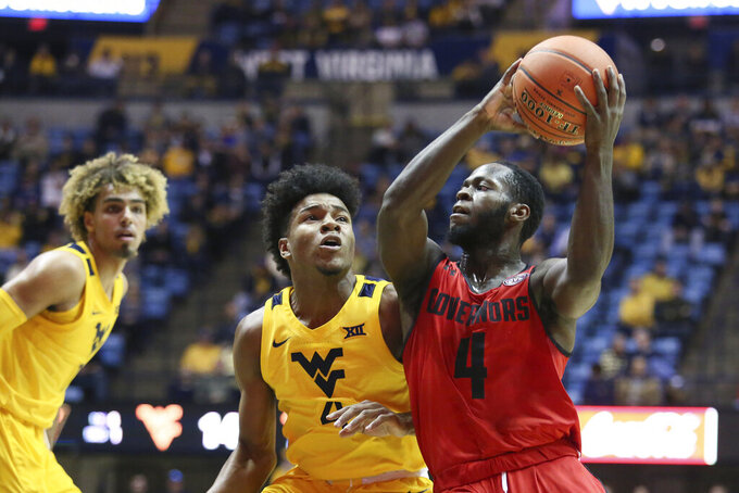 Austin Peay guard Antwuan Butler (4) goes to pass the ball as he is defended by West Virginia guard Miles McBride (4) and West Virginia forward Emmitt Matthews Jr., left, looks on during the first half of an NCAA college basketball game Thursday, Dec. 12, 2019, in Morgantown, W.Va. (AP Photo/Kathleen Batten)