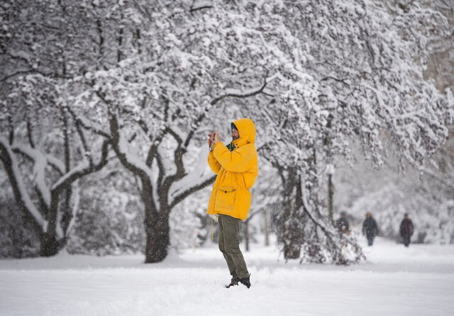 A person takes a photo with their phone during a major snowstorm in Ottawa on Saturday, Jan. 16, 2021.   (Justin Tang/The Canadian Press via AP)
