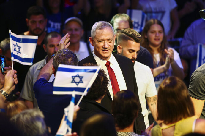 FILE - In this Sunday, Sept. 15, 2019 file photo, Blue and White party leader Benny Gantz is surrounded by his supporters as he arrives to election campaign in Tel Aviv, Israel. Israel will hold general elections on Sept. 17. Israel heads to the polls on Tuesday for the second time this year. After drawing even with Likud in April, with 35 seats apiece, the Blue and White party, headed by former army chief Benny Gantz, remains Netanyahu's main rival. (AP Photo/Oded Balilty, File)