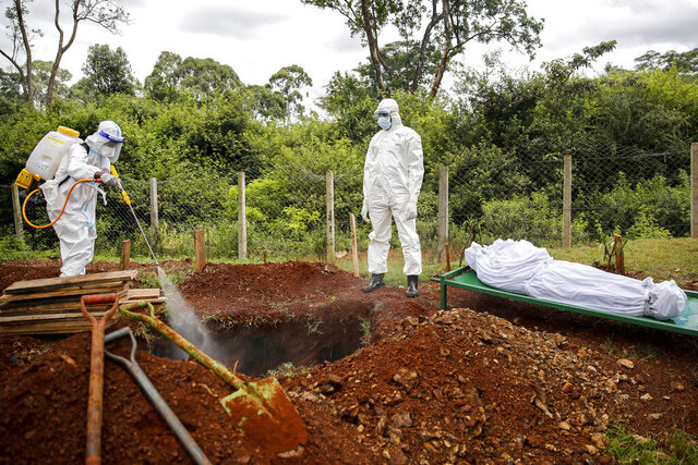 Members of a team dedicated to burying Muslim victims of the new coronavirus spray disinfectant into the grave before burying Mohamed Ali Hassan, whose cousin said had been unaware he had the new coronavirus and died in his house in the Eastleigh area, at the Langata Muslim cemetery in Nairobi, Kenya Thursday, May 7, 2020. The Kenyan government on Wednesday sealed off the Eastleigh area of the capital Nairobi and the Old Town area of the port city of Mombasa, with no movement permitted in or out for 15 days, due to