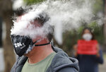 In this June 2, 2020 photo, a demonstrator exhales smoke while wearing a face mask during a  protest against the tobacco ban outside parliament in Cape Town, South Africa. An effort to lift South Africa's ban on cigarette sales during the country's coronavirus lockdown has failed. The High Court in the capital, Pretoria, on Friday, June 26, 2020 dismissed a bid by the Fair Trade Independent Tobacco Association, which represents smaller manufacturers. (AP Photo/Nardus Engelbrecht)
