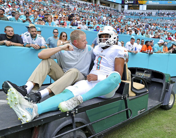 Miami Dolphins quarterback Tua Tagovailoa (1) carted out the field after getting injured in a play during the first quarter of an NFL football game against the Buffalo Bills at Hard Rock Stadium, Sunday, Sept. 19, 2021 in Miami Gardens, Fla. A battery of tests run on Tagovailoa failed to show any serious problems other than bruised ribs, raising at least the possibility that he could play next weekend when the Dolphins (1-1) visit the Las Vegas Raiders (2-0). (David Santiago/Miami Herald via AP)