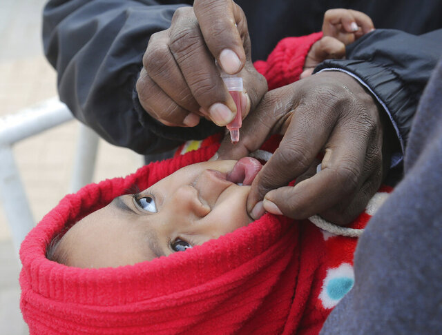 A Pakistani health worker gives polio vaccine drops to a child in Lahore, Pakistan, Wednesday, Dec. 18, 2019. Gunmen in Pakistan shot and killed the two policemen on Wednesday who were part of the most recent anti-polio drive in the country's rugged and volatile northwest, officials said. (AP Photo/K.M. Chaudary)