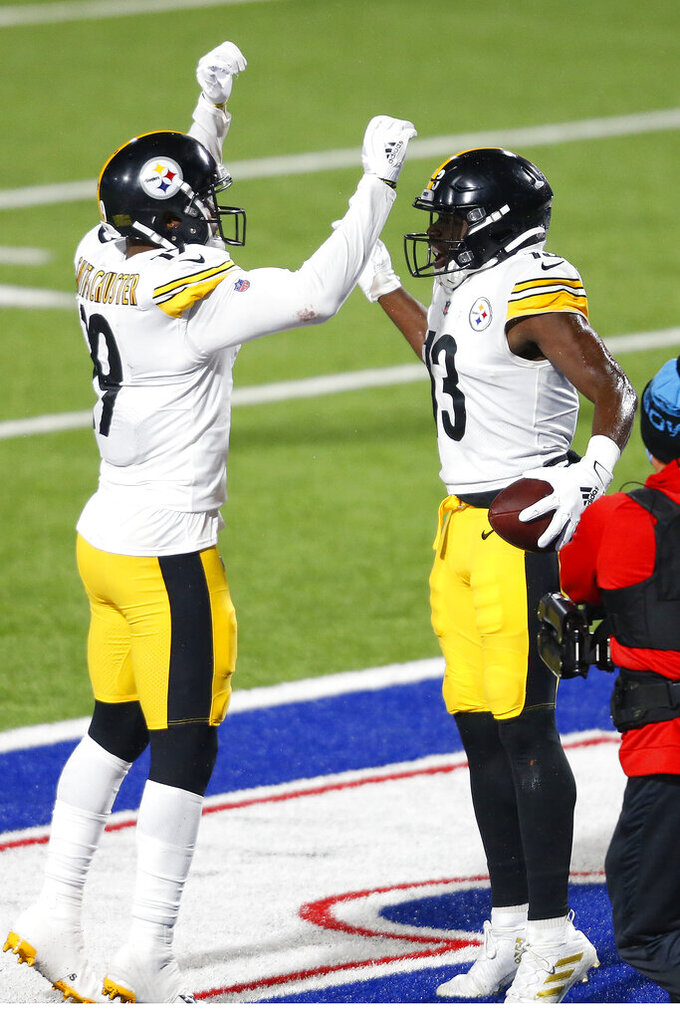 Pittsburgh Steelers wide receiver James Washington (13) celebrates with JuJu Smith-Schuster (19) after scoring on a 19-yard pass play with Buffalo Bills cornerback Levi Wallace (39) defending during the first half of an NFL football game in Orchard Park, N.Y., Sunday, Dec. 13, 2020. (AP Photo/Adrian Kraus)