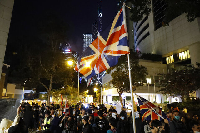 Protesters wave a British flag as they gather for a rally outside of the British Consulate in Hong Kong, Friday, Nov. 29, 2019. Hong Kong police ended their blockade of a university campus Friday after surrounding it for 12 days to try to arrest anti-government protesters holed up inside. (AP Photo/Vincent Thian)