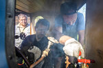 Pavel Chilin's assistants Sergei Terekhov, center, and Vadim Gukov drive a locomotive on Pavel Chilin's personal railway in Ulyanovka village outside St.Petersburg, Russia Sunday, July 19, 2020. It took Chilin more than 10 years to build the 350-meter-long miniature personal narrow-gauge railway complete with various branches, dead ends, circuit loops, and even three bridges. (AP Photo/Dmitri Lovetsky)