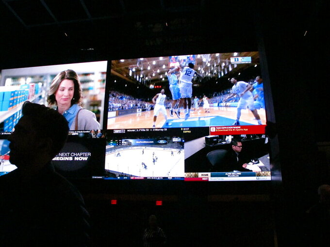 This March 8, 2019 photo shows a fan watching the first day of the March Madness college basketball tournament at the Borgata casino in Atlantic City N.J. Figures released by state gambling regulators on Thursday, April 25, 2019 show more than $106 million was wagered on the NCAA basketball championship tournament in New Jersey _ three times the amount wagered on the Super Bowl. (AP Photo/Wayne Parry)