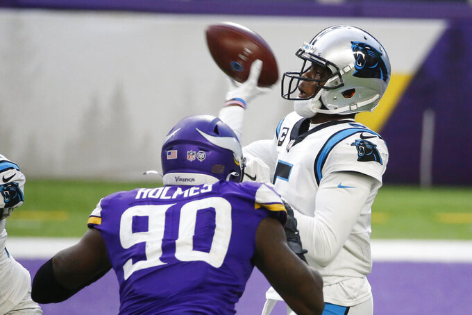 Carolina Panthers quarterback Teddy Bridgewater throws a pass over Minnesota Vikings defensive end Jalyn Holmes (90) during the second half of an NFL football game, Sunday, Nov. 29, 2020, in Minneapolis. The Vikings won 28-27. (AP Photo/Bruce Kluckhohn)