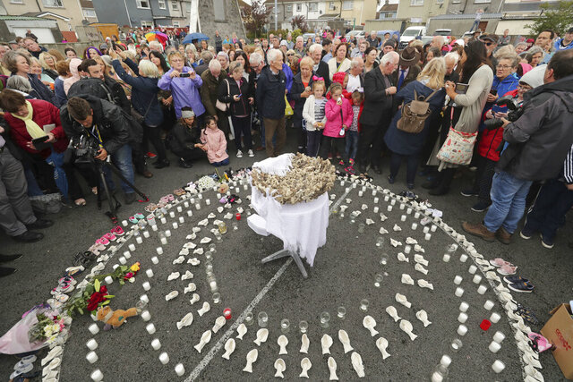 "FILE - In this Aug. 26, 2018 file photo, People gather to protest at the site of the former Tuam home for unmarried mothers in County Galway, Ireland. The Vatican has indicated its support for a campaign to exhume the bodies of hundreds of babies who were buried on the grounds of a Catholic-run Irish home for unwed mothers to give them a proper Christian burial. The Vatican's ambassador to Ireland, Archbishop Jude Thaddeus Okolo, said in a July 15, 2020 letter to the amateur Irish historian behind the campaign that he shared the views of the archbishop of Tuam, Ireland, Michael Neary, who has said it was a ""priority"" for him to re-inter the bodies in consecrated ground. (Niall Carson/PA via AP, file)"