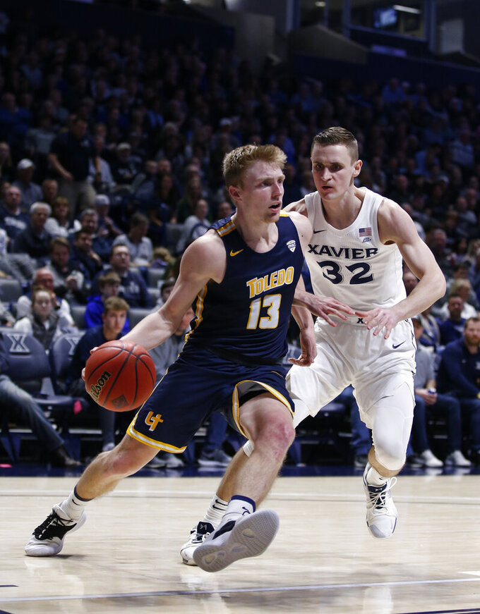 Toledo guard Jaelan Sanford (13) drives to the basket against Xavier forward Ryan Welage (32) during the second half of a first-round NIT college basketball game Wednesday, March 20, 2019, in Cincinnati. Xavier won 78-64. (AP Photo/Gary Landers)