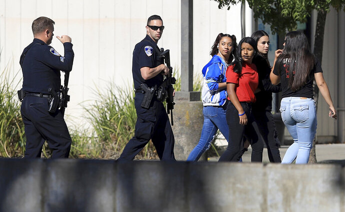 Ridgeway High School students are led back to their classes after the arrest of a suspect who opened fire from on another student across the street from the high school , Tuesday, Oct. 22, 2019 in Santa Rosa, Calif. (Kent Porter/The Press Democrat via AP)
