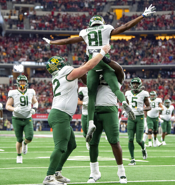 Baylor wide receiver Tyquan Thornton (81) celebrates with offensive linemen Sam Tecklenburg, left, and Xavier Newman, lifting Thornton, during the first half of an NCAA college football game against Oklahoma for the Big 12 Conference championship, Saturday, Dec. 7, 2019, in Arlington, Texas. (AP Photo/Jeffrey McWhorter)