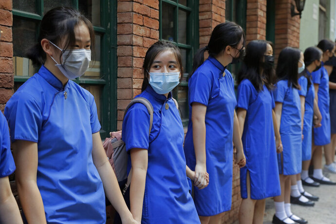 Students wearing mask hold hands to surround St. Stephen's Girls' College in Hong Kong, Monday, Sept. 9, 2019. Thousands of demonstrators in Hong Kong urged President Donald Trump to