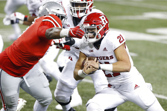 Rutgers quarterback Johnny Langan, right, cuts upfield against Ohio State defensive lineman Taron Vincent during the second half of an NCAA college football game Saturday, Nov. 7, 2020, in Columbus, Ohio. Ohio State won 49-27. (AP Photo/Jay LaPrete)
