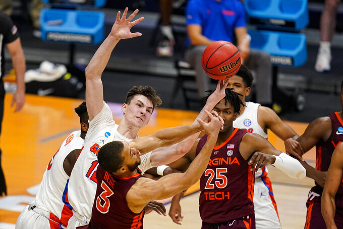 Florida forward Colin Castleton (12) grabs a rebound over Virginia Tech guard Wabissa Bede (3) in the second half of a first round game in the NCAA men's college basketball tournament at Hinkle Fieldhouse in Indianapolis, Friday, March 19, 2021. (AP Photo/Michael Conroy)