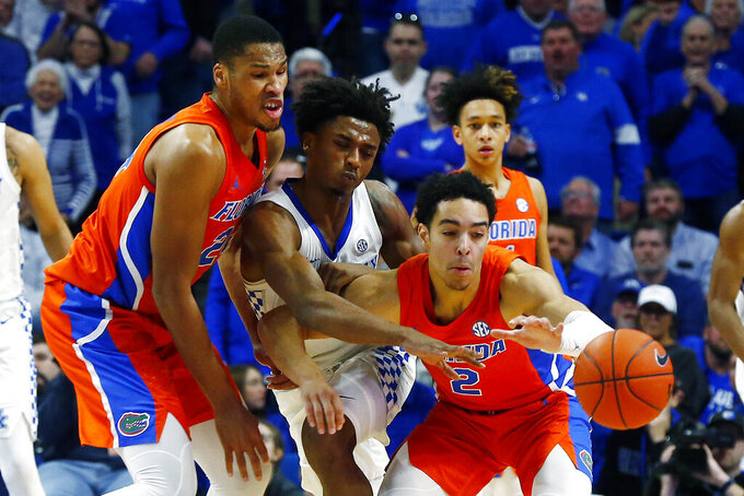Kentucky's Ashton Hagans, middle, is sandwiched between Florida's Andrew Nembhard (2) and Kerry Blackshear Jr., left, in the second half of an NCAA college basketball game in Lexington, Ky., Saturday, Feb. 22, 2020. Kentucky won 65-59. (AP Photo/James Crisp)
