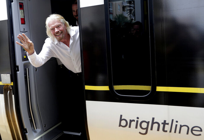 FILE - In this April 4, 2019, file photo Richard Branson, of Virgin Group, waves as he arrives on a Brightline train in West Palm Beach, Fla. The Brightline, a higher-speed passenger train service tied to Richard Branson's Virgin Group, has the worst per-mile death rate in the U.S. . (AP Photo/Lynne Sladky, File)