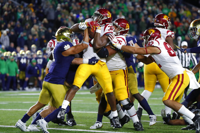 Southern California running back Markese Stepp (30) is lifted into the end zone by teammate Alijah Vera-Tucker (75) as Notre Dame safety Alohi Gilman defends in the second half of an NCAA college football game in South Bend, Ind., Saturday, Oct. 12, 2019. (AP Photo/Paul Sancya)
