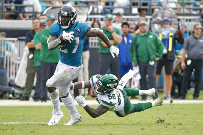 Jacksonville Jaguars running back Leonard Fournette tries to get past New York Jets linebacker James Burgess during the second half of an NFL football game, Sunday, Oct. 27, 2019, in Jacksonville, Fla. (AP Photo/Stephen B. Morton)