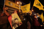Supporters of Hezbollah leader Sayyed Hassan Nasrallah hold his pictures and waves Hezbollah flags in the southern suburb of Beirut, Lebanon, Friday, Oct. 25, 2019. Leader of Lebanon's Hezbollah calls on his supporters to leave the protests to avoid friction and seek dialogue instead. The army and special forces deployed along the road outside Hezbollah's stronghold known as Dahiyeh, apparently to prevent renewed friction. Members of Hezbollah also deployed on entrance and exits to Dahiyeh, in a clear move to block supporters from heading to central Beirut. (AP Photo/Hassan Ammar)