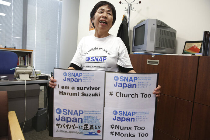 FILE - In this Nov. 25, 2019, file photo, Survivors Network of Those Abused by Priests (SNAP) Japan local leader Harumi Suzuki holds signs while speaking during an interview with The Associated Press in Tokyo. Suzuki has filed a suit against the Roman Catholic Church in Japan alleging that a priest raped her four decades ago, as the church's unfolding worldwide sexual abuse crisis gradually reaches Japan. (AP Photo/Koji Sasahara, File)
