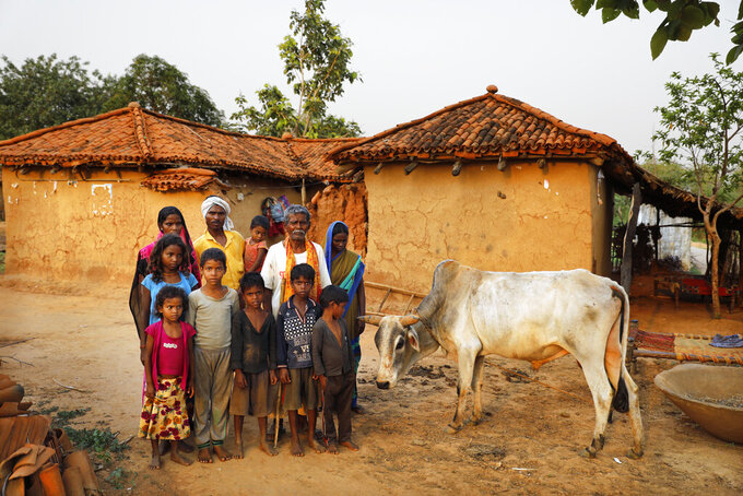 Munni Kol, 70, in white, with his son Bishambar Kol, daughters-in-law, Asha and Manju, and his grandchildren pose for a photograph in front of their home, in Jamsoti village, Uttar Pradesh state, India, on June 8, 2021. Kol got himself vaccinated against the coronavirus, where as his family has refused to. India's vaccination efforts are being undermined by widespread hesitancy and fear of the jabs, fueled by misinformation and mistrust. That's especially true in rural India, where two-thirds of the country's nearly 1.4 billion people live. (AP Photo/Rajesh Kumar Singh)