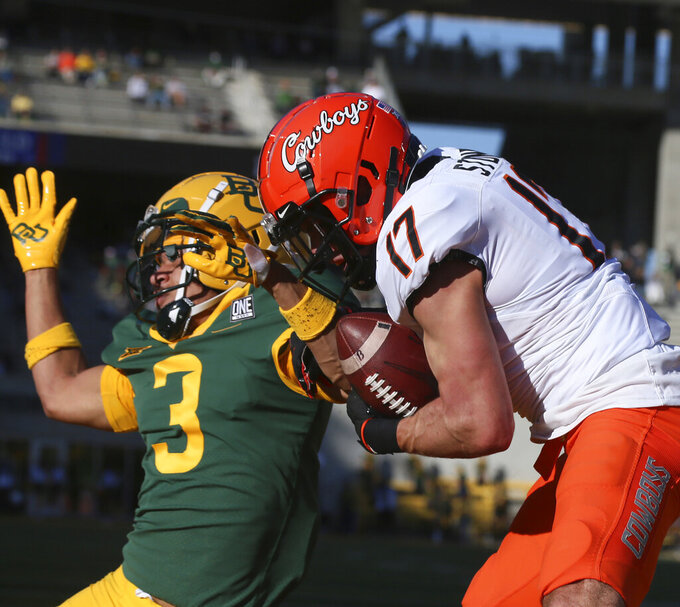 Oklahoma State wide receiver Dillon Stoner, right, pulls down a touchdown pass over Baylor cornerback Raleigh Texada, left, in the first half of an NCAA college football game, Saturday, Dec. 12, 2020, in Waco, Texas. (Rod Aydelotte/Waco Tribune-Herald via AP)