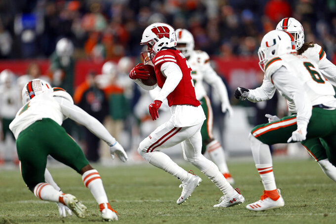 Wisconsin wide receiver Kendric Pryor (3) runs away from Miami defensive back Jhavonte Dean (6) for a touchdown during the first half of the Pinstripe Bowl NCAA college football game Thursday, Dec. 27, 2018, in New York. (AP Photo/Adam Hunger)
