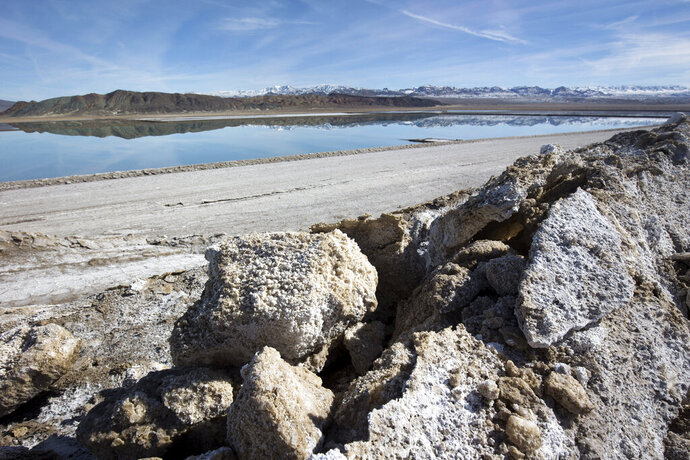 FILE - In this Jan. 30, 2017, file photo, waste salt, foreground, is shown near an evaporation pond at the Silver Peak lithium mine near Tonopah, Nev.  The Trump administration granted final approval for a proposed northern Nevada lithium mine, one of several eleventh-hour moves made by the Department of Interior to greenlight mining and energy projects. Unlike some other approvals, which are likely to be revoked, President Biden has voiced support for lithium mining as part of his clean energy plans.  (Steve Marcus/Las Vegas Sun via AP, File)