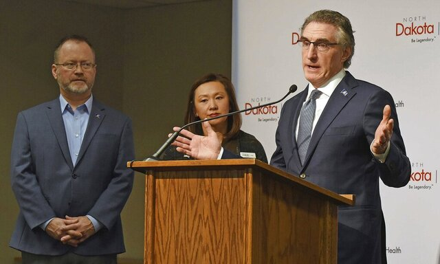 FILE - In this March 12, 2020, file photo, North Dakota Gov. Doug Burgum, right, speaks on the first case of the coronavirus in North Dakota, during a news conference held with officials with the state health department in Bismarck, N.D. Gov. Listening at left are Lt. Gov. Brent Sanford and State Health Officer Mylynn Tufte.  Burgum gave a sobering message Thursday, March 26, to people who are complaining that some of the counties identified with patients who have contracted the coronavirus aren't accurate: COVID-19 is coming to your county. (Tom Stromme/The Bismarck Tribune via AP, File)