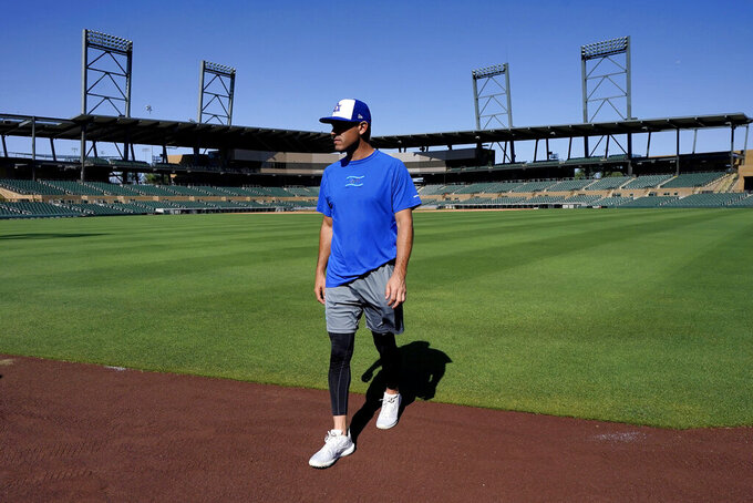 Israel Olympic baseball player Ian Kinsler walks along the outfield warning track at Salt River Fields spring training facility, Wednesday, May 12, 2021, in Scottsdale, Ariz. Israel has qualified for the six-team baseball tournament at the Tokyo Olympic games which will be its first appearance at the Olympics in any team sport since 1976. (AP Photo/Matt York)