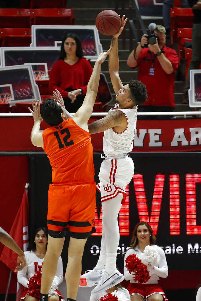 Utah forward Timmy Allen, right, shoots as Oregon State center Roman Silva (12) defends in the first half during an NCAA college basketball game Thursday, Jan. 2, 2020, in Salt Lake City. (AP Photo/Rick Bowmer)