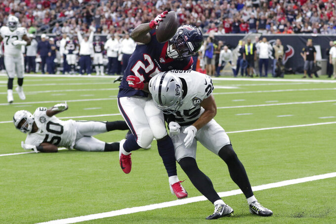 Houston Texans running back Duke Johnson (25) is hit by Oakland Raiders free safety Erik Harris (25) as he scores on a touchdown catch during the first half of an NFL football game Sunday, Oct. 27, 2019, in Houston. (AP Photo/Michael Wyke)