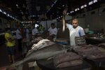 In this Sept. 7, 2019 photo, a fish vendor waits for customers after sharpening his knife inside the Ver-o-Peso riverside market in Belém, Brazil. The market sells Amazonian river fish like dourada or the giant piracucu, which can grow as long as 10 feet and weigh more than 400 pounds. (AP Photo/Rodrigo Abd)