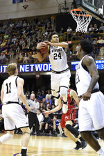 Wofford forward Keve Aluma (24) drives the ball to the basket past VMI guard Garrett Gilkeson (2) as Wofford guards Ryan Larson (11) and Tray Hollowell (21) look for the rebound in the second half of an NCAA college basketball game for the Southern Conference basketball tournament championship, Saturday, March 9, 2018, in Asheville, N.C. Wofford won 99-72. (AP Photo/Kathy Kmonicek)