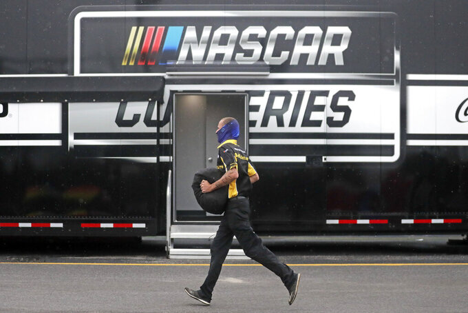 A crew member for driver Timmy Hill runs through the infield in the rain before the Toyota 500 NASCAR Cup Series auto race Wednesday, May 20, 2020, in Darlington, S.C. (AP Photo/Brynn Anderson)