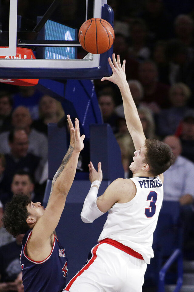 Gonzaga forward Filip Petrusev, right, shoots over Saint Mary's forward Dan Fotu during the first half of an NCAA college basketball game in Spokane, Wash., Saturday, Feb. 29, 2020. (AP Photo/Young Kwak)