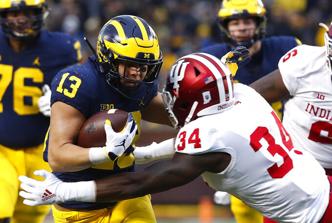 Michigan running back Tru Wilson (13) is brought down by Indiana linebacker Cam Jones (34) in the first half of an NCAA college football game in Ann Arbor, Mich., Saturday, Nov. 17, 2018. (AP Photo/Paul Sancya)