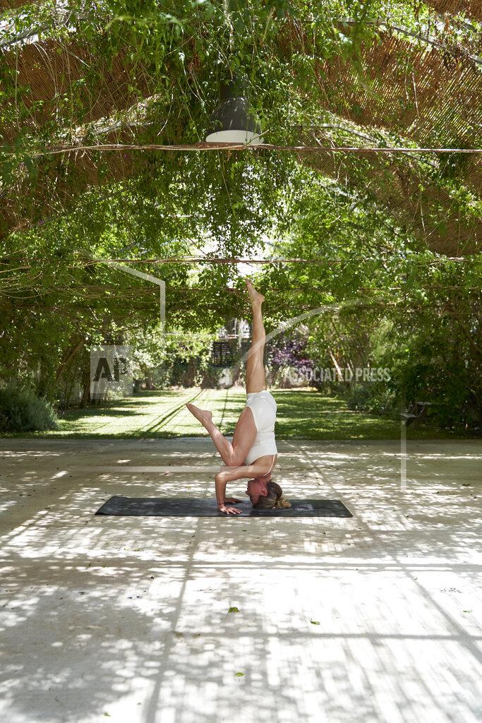 Mature woman practicing headstand on yoga mat in backyard garden