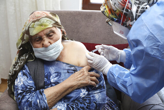 In this photo provided by Turkey's Health Ministry, a vaccination team member administers a dose of the CoronaVac vaccine, produced by China's Sinovac Biotech Ltd., to Sati Kayiran, 88, in Ayas, in Ankara province, Turkey, Thursday, Jan. 21, 2021. Turkey on Thursday expanded its COVID-19 inoculation campaign to include people aged 85 and older. (Turkish Health Ministry via AP)