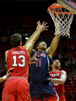 Arizona forward Ira Lee (11) attempts a shot between Utah forwards Novak Topalovic, left, and Timmy Allen, right, during the first half of an NCAA college basketball game Thursday, Feb. 14, 2019, in Salt Lake City. (AP Photo/Alex Goodlett)