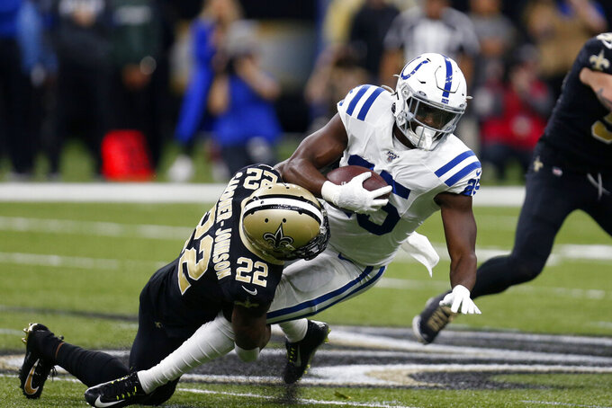 New Orleans Saints defensive back Chauncey Gardner-Johnson (22) tackles Indianapolis Colts running back Marlon Mack (25) in the first half of an NFL football game in New Orleans, Monday, Dec. 16, 2019. (AP Photo/Butch Dill)