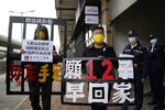 FILE - In this Dec. 10, 2020, file photo, pro-democracy activists Leung Kwok-hung, left, and Raphael Wong Ho-ming holding placards, demand the release of the 12 Hong Kong activists detained at sea by Chinese authorities as they march to the Chinese central government's liaison office, in Hong Kong. A Chinese lawyer who represented a Hong Kong pro-democracy activist was stripped of his law license on Friday, Jan. 15, 2021,  amid efforts by Beijing to crush opposition to its tighter control over the territory. The placards read