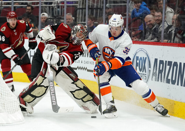 Arizona Coyotes goaltender Antti Raanta (32) and New York Islanders left wing Ross Johnston fight for the puck in the first period during an NHL hockey game, Monday, Feb. 17, 2020, in Glendale, Ariz. (AP Photo/Rick Scuteri)